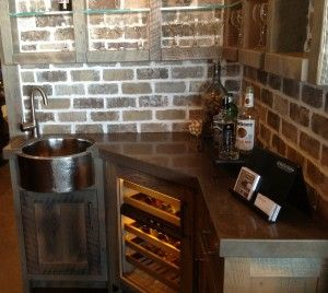 Brick wall, possibly barn wood cabinets and shelves, and I love whatever the corner with sink is made from.