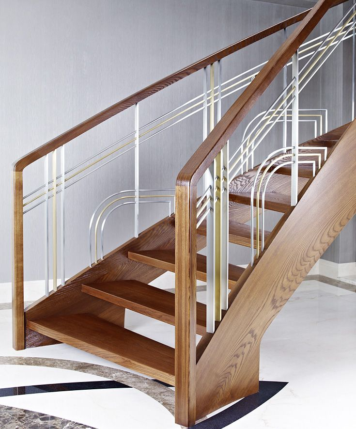 ST770 Curved stringer stair made of thermo ash. Balustrade of stainless steel and brass with wooden handrail. Private residential project, designed by Anna Wichłacz&TRĄBCZYŃSKI.