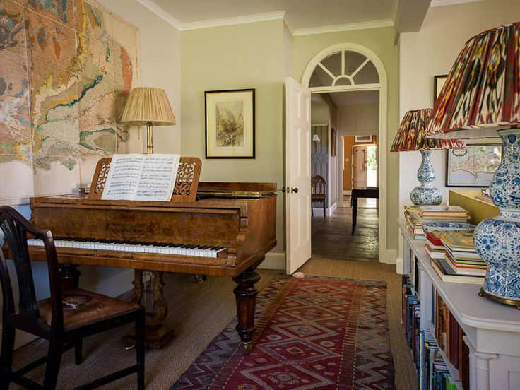 Beautiful room....the low bookcases, wood floor, rug, lamps, arched doorway, not the mention the piano (Dorset | Ben Pentreath Ltd)