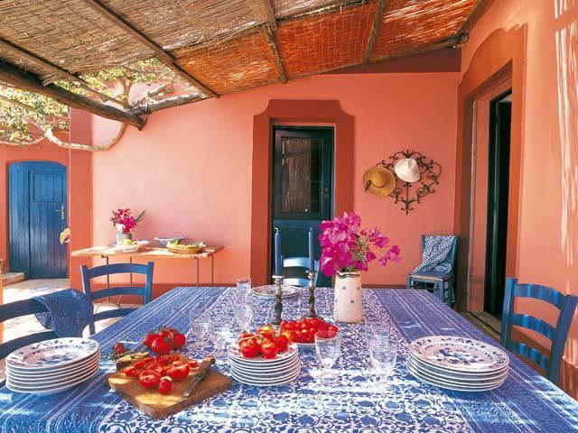 D'estate si vive molto fuori. Il terrazzo della cucina diventa la sala da pranzo, e una tettoia di legno e canniccio ripara dal sole.