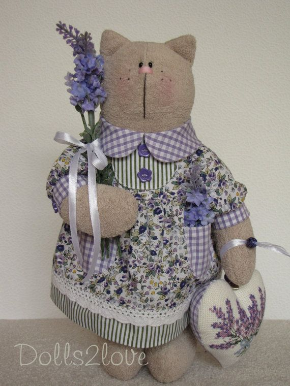 Tilda Cat Suzy wearing a purple dress made from liberty and gingham fabric, holding a bunch of lavender and a hand-embroidered heart, made by Dolls2love on Etsy, €60.00. (sold)