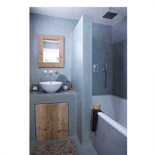 Dans béton gris clair et une baignoire blanche qui se transforme en douche italienne dans une petite salle de bain aménagée gaine de place avec un placard de rangement sous le plan vasque construit sur mesure