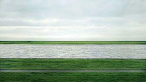 """Andreas Gursky: """"Rhein II"""" (1999). Técnica: Digital, impreso con plexiglas. Corriente: Escuela de Düsseldorf, arquitectura, objetividad."""