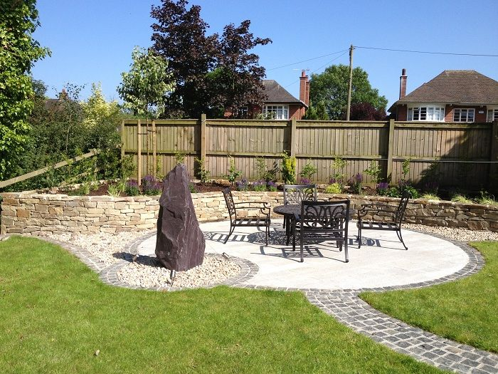 curved granite sett path leading to large circular patio and slate monolith water feature www - Garden Design Cheshire