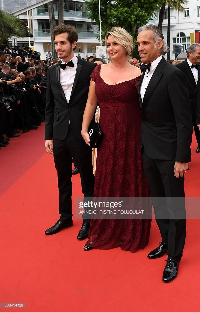Former racing driver Paul Belmondo (R), his wife Luana Tenca and their son Victor pose as they arrive on May 22, 2016 for the closing ceremony of the 69th Cannes Film Festival in Cannes, southern France. / AFP / ANNE
