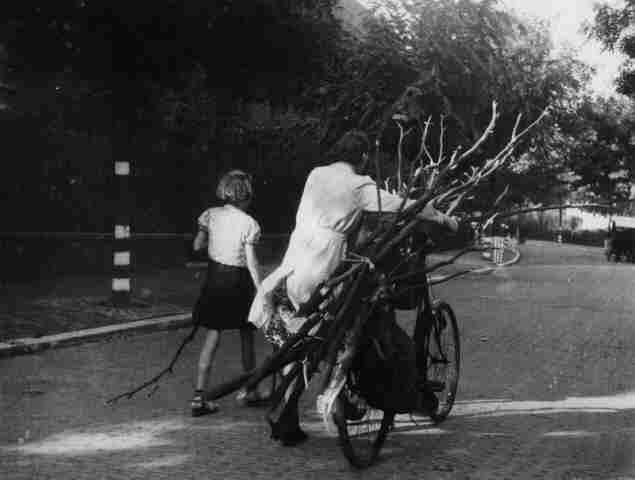 Schaarste aan brandstof gedurende de bezettingstijd. Een vrouw met meisje vervoeren per fiets gesprokkeld hout. Foto van J. van Rhijn. Datering: 1944 t/m 1945.