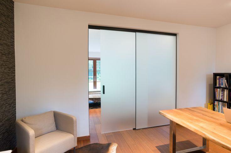 Glazen schuifdeur met vast paneel op maat gemaakt door Anyway Doors. Uitgevoerd in gezuurd glas met zwarte aluminium profielen en grepen.