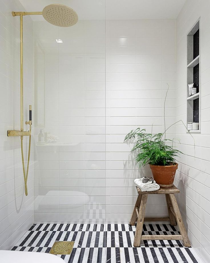 black and white striped tile in the bathroom gold fixtures an oversized shower head