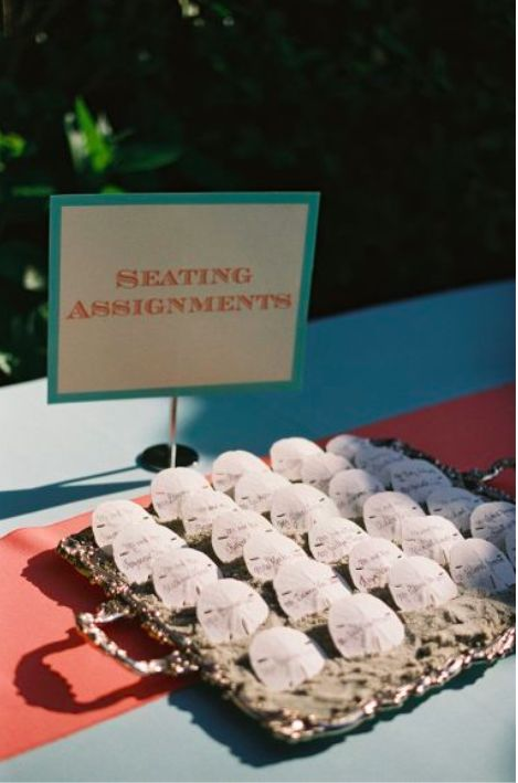 use sand dollars as a creative way to direct guests to the right table for a