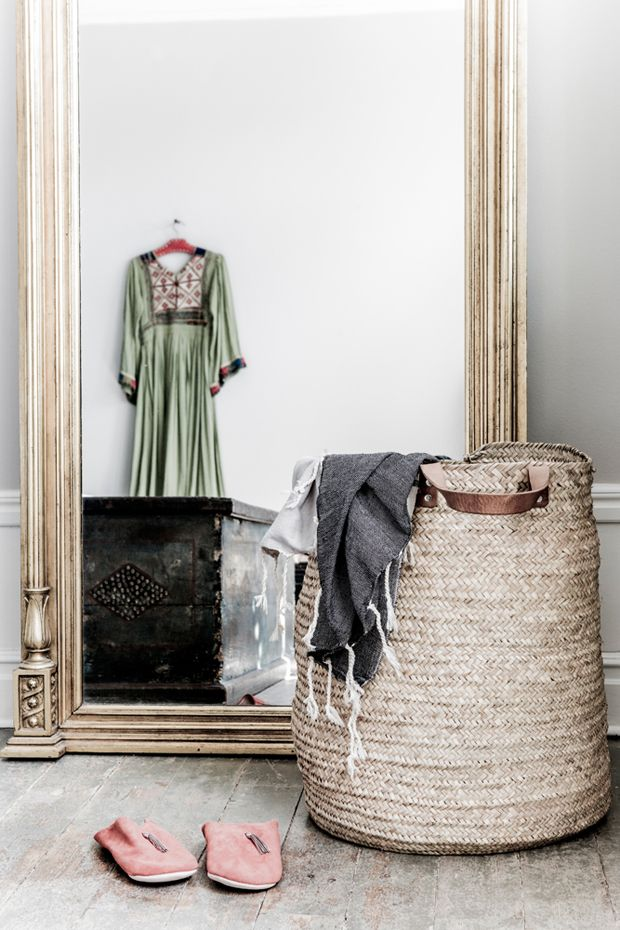 Gilded mirror, basket and slippers in the wonderfully relaxed, boho Skåne home of Malin Persson. Photo: Lina Roos.