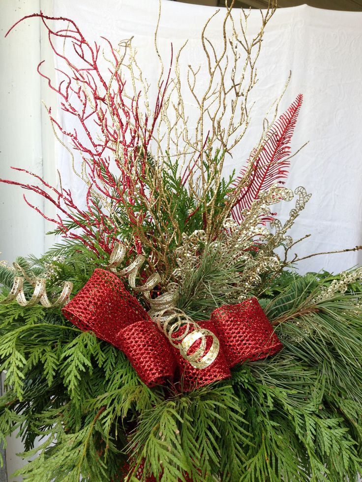Festive colors of picks and Sprays are used to add texture and color to this Christmas arrangement