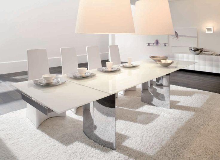 table à manger extensible et blanche dotée de deux grands pieds métalliques et entourée de chaises blanches
