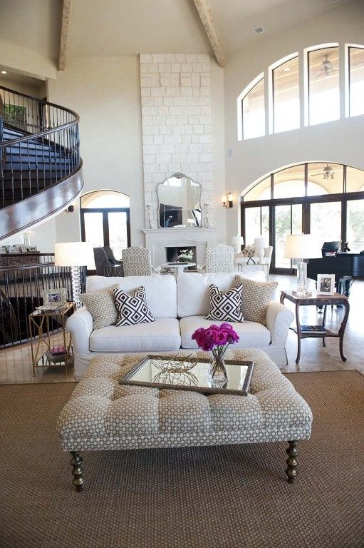 Casual neutral living room, tuffted square ottoman, which couch, winding staircase, high beam ceilings