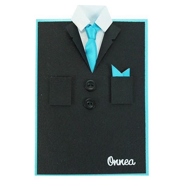 Puku ja paita syntyvät papereista. Satiininauhasta on kiepautettu oikea kravattisolmu ja se on kiinnitetty paperipaidan kaulukseen.