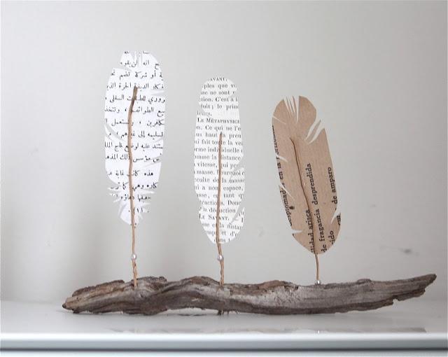 trois plumes de papier sur un bois flotté