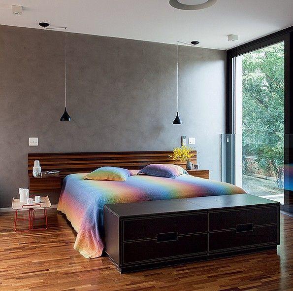 O quarto do casal possui grandes portas de correr, que abrem totalmente o ambiente para um amplo terraço. Na parede, a pintura imita concreto. Projeto da arquiteta Monica Drucker