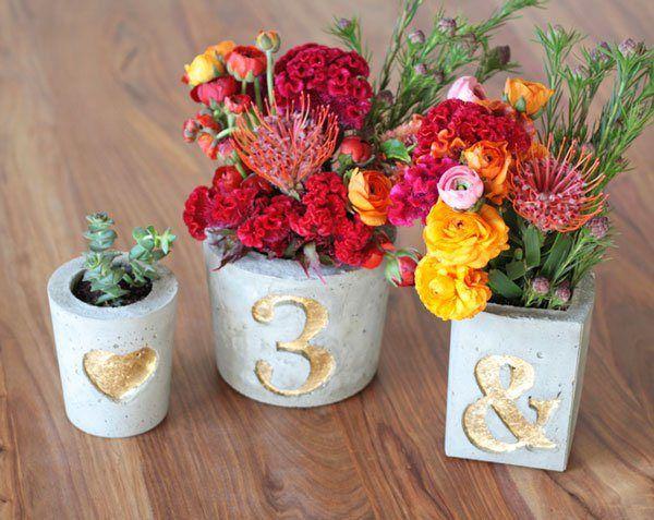 Centros de mesa con floreros y bases de concreto con números para un estilo rústico o moderno. #CentrosDeMesa