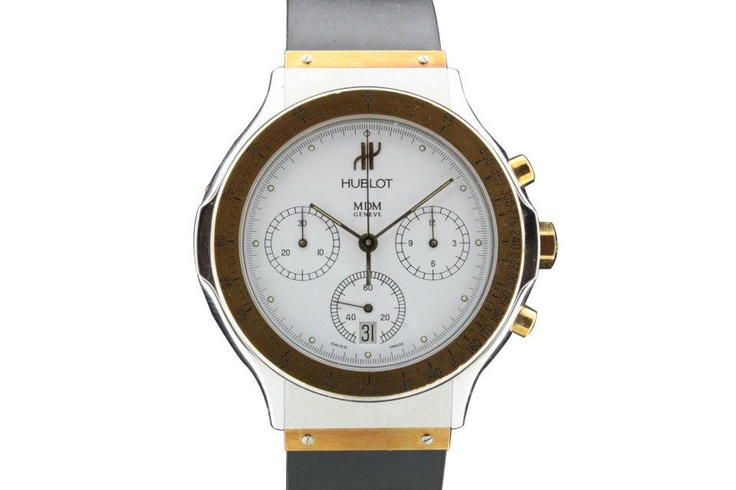 """Hublot, Ref. 1620.2, case No. 204874. Water-resistant to 5 atm., stainless steel and yellow gold quartz gentleman's wristwatch with round button chronograph, registers, tachometer and date, with rubber strap with gold leaves integrated and inserted in patented central attachment, gold and steel original double deployant clasp, white dial with """"baton"""" hands. Accompanied by fitted box and certificate of guarantee."""