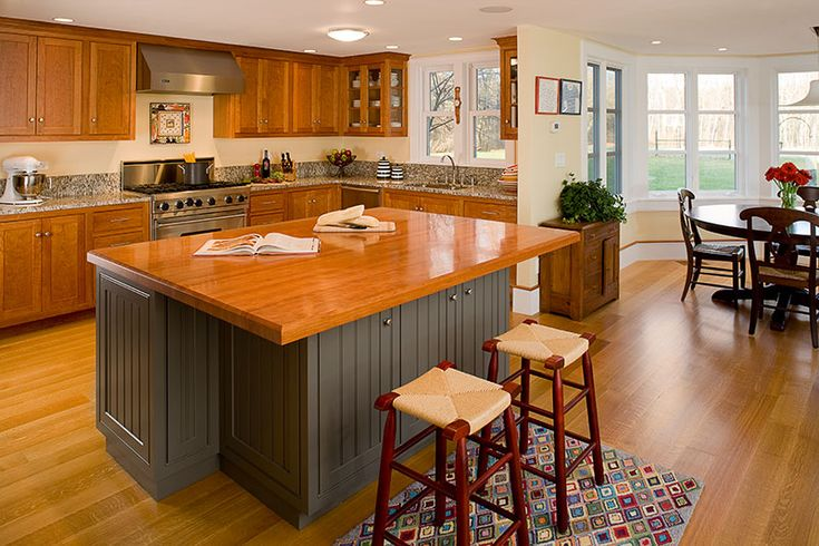 Combination of cherry and blue painted custom kitchen cabinetry with a cherry island top and quarter sawn oak floor in Carlisle, MA