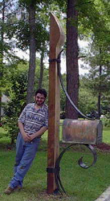 tall post with wrought iron to hold mailbox
