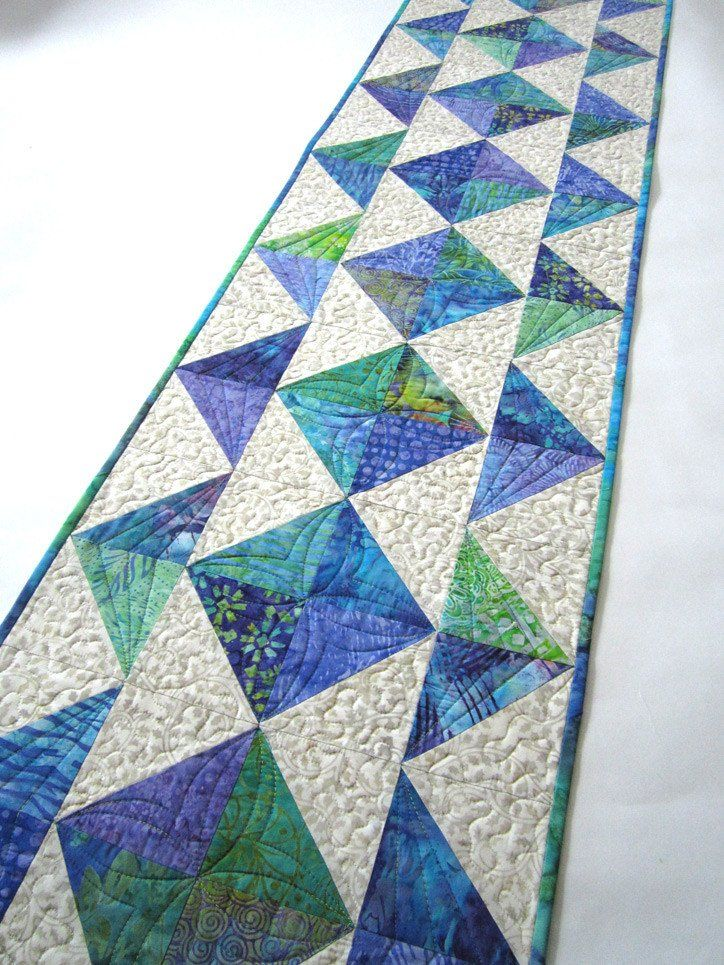 This table runner is made using batik fabrics in a variety of teal, turquoise and purple colors. This runner will be a beautiful setting for your table. This runner would also be a wonderful gift to g