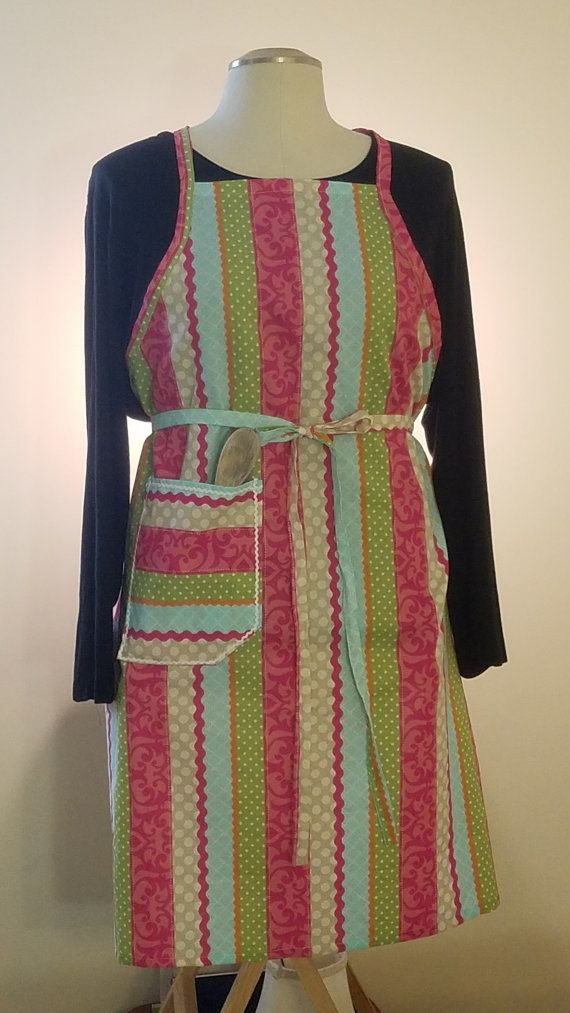 Never a dull moment in the kitchen with this full size French Provence apron. This colorful apron has vertical stripes of pink, green, light blue and grey. Each stripe has a design printed in it. There is a large pocket outlined with small white rick- rack on the right side. This apron is perfect for the contemporary hostess and is great for everyday use. The apron is made of 100% cotton. Cleaning is simple. Cool wash and low dry with possibly a little pressing is all that is needed.  Length…