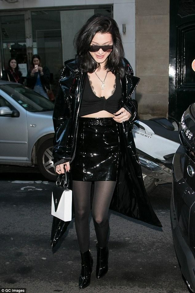 Bella Hadid wearing Area Mirrored Sunglasses, Giuseppe Zanotti Patent Booties, Karl Lagerfeld K/Signature Clutch, Brashy Berlin PVC Trenchcoat, Wolford Velvet De Luxe 66 Tights in Anthracite and Manokhi Fusta Skirt