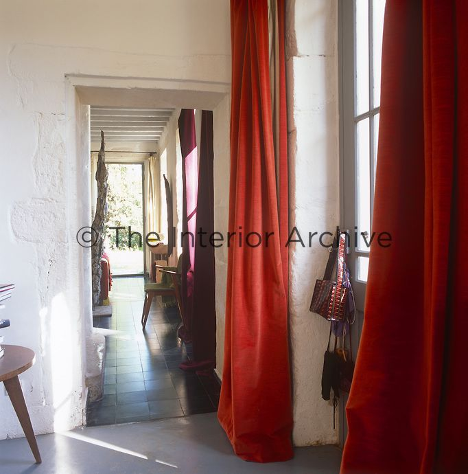 Saint-Remy-de-Provence - Red velvet curtains hang on either side of a door and an open doorway gives a view to a room beyond with a tiled floor.