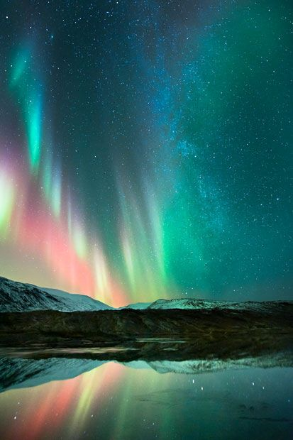 A pink aurora dances in the sky at Rana in Nordland, Norway