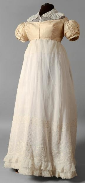 Drouot.com, listing in French. Rough translation: Skirt, bodice/jacket, and chemisette, 1815-1820. Organdy skirt ruffled and embroidered with daisies and garlands. Spencer of woven birdseye pattern silk, gathered sleeves, with pleats and knots; neckline trimmed with braid of satin; back lacing. Chemisette with large ruffled collar [may date later than 1820].