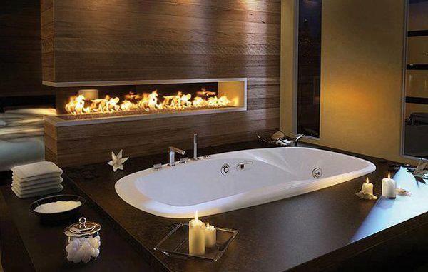 Большая ванная комната больше напоминает спа с гидромассажной ванной и газовым камином. .