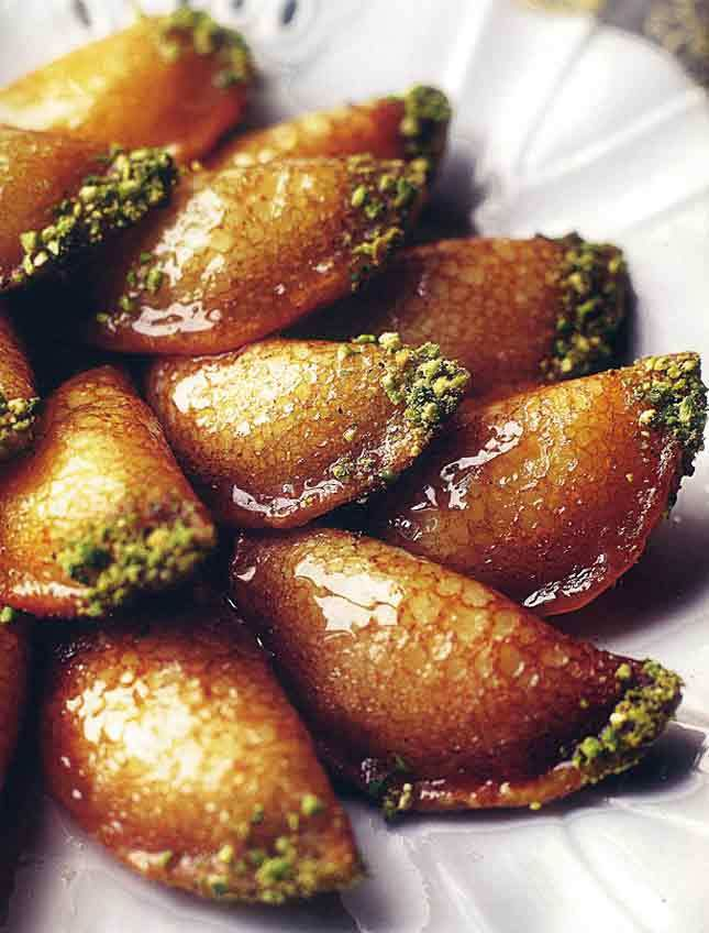 Atayef – stuffed syrian pancakes filled with ricotta cheese, deep-fried, dipped in chopped pistachio nuts, and topped with shira (Fragrant Aleppian Dessert Syrup)