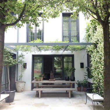 Aménager une terrasse ombragée par de la verdure sous le patio, une idée sympa pour s'abriter du soleil pendant l'été. Sur la structure du  toit en fer court de la glycine qui préserve l'intimité et l'effet de cocon est renforcé par un mur végétal de jasmin grimpant sur toute la hauteur du mur de clôture avec les voisins. Deux bancs et une table de jardin en bois attentent amis et famille pour partager des repas sur la terrasse dans un cadre agréable.