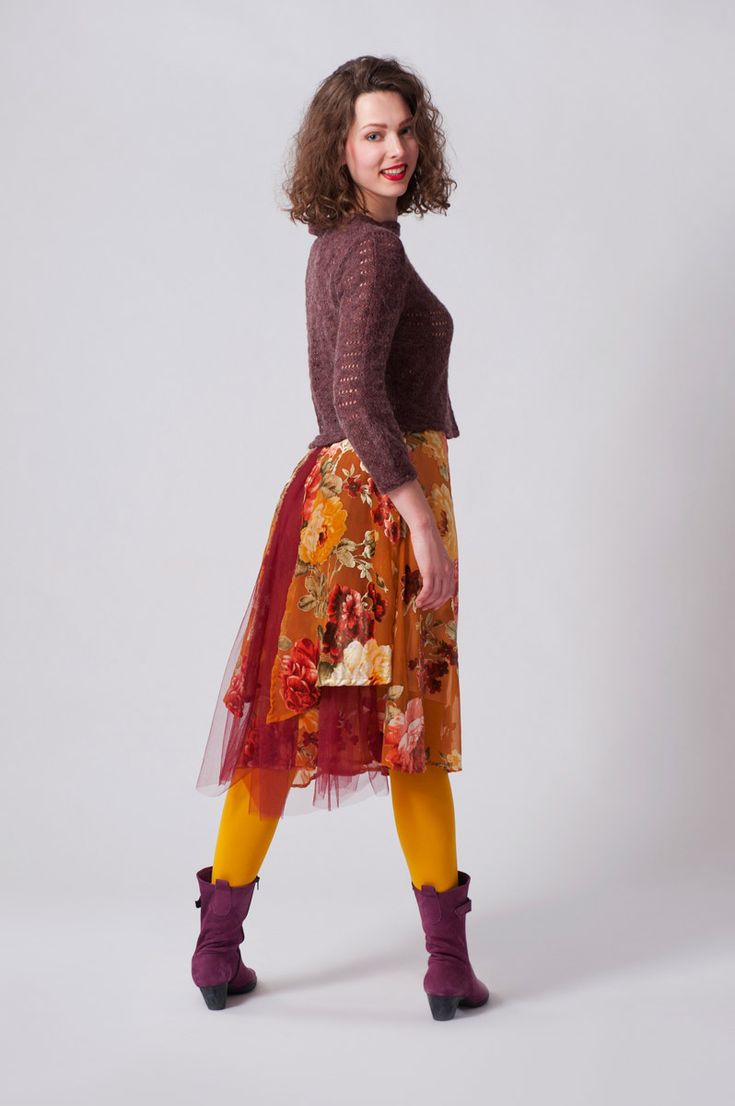 Okergele rok met rode bloemen van dunne velours stof, gecombineerd met verschillende lagen rode tule. Kort lichtpaars truitje met ballonmouwen van een mengsel van wol en synthetisch materiaal.