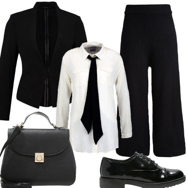 Bianco e nero per la composizione in stile maschile, composta da una camicia bianca con fiocco lungo nero, che somiglia ad una cravatta, accostata ad un paio di pantaloni palazzo e giacca nera, Le scarpe sono delle stringate nere, come la borsa a mano: semplice, essenziale ed elegante.