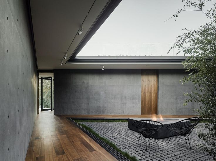 Internal courtyard that isn't open to the living, but is defined by the corridors within.  Like the use of cobblestone to the courtyard with a small strip of green around the edges up against the timber flooring and concrete.   Oak Pass House / Walker Workshop