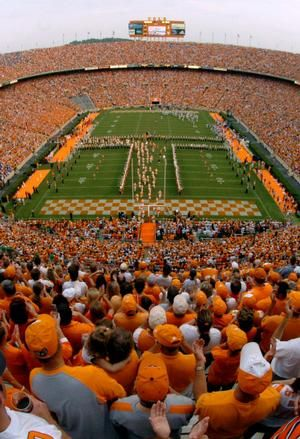 "The University of Tennessee football team runs through the 'T' as fans cheer them on before the start of the game against the Air Force at Neyland Stadium in Knoxville. UT today announced a full smoking ban at Neyland Stadium, to comply with the ""Non-Smoker Protection Act"" passed by the state Legislature this year."