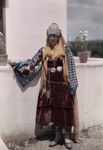 Woman wears the dress of Astypalaia, one of the Dodecanese.  Keywords: COLOR IMAGE, PHOTOGRAPHY, OUTDOORS, DAY, AUTOCHROME, VINTAGE COLLECTION, ONE PERSON, MID ADULTS, MID ADULT WOMEN, REENACTMENTS, COSTUMES, ANTIQUITIES, DELPHIC FESTIVAL, EMBROIDERY, HEADDRESS, STANDING, FULL FRAME, FRONT VIEW, ASTYPALAIA  Location: Greece.  Photographer: MAYNARD OWEN WILLIAMS/National Geographic Creative