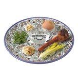 Passover Seder of roasted egg, roasted bone, parsley, charoset, celery, nuts and salt water on plate