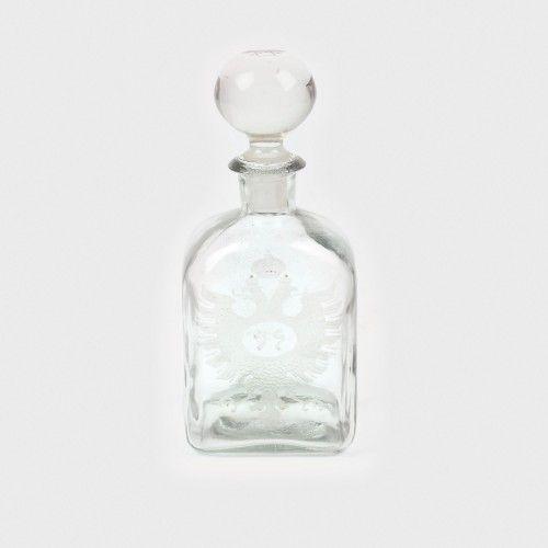 Flacon din sticlă pentru băuturi tari, decorat cu acvila bicefală și steaua lui David, sfârșitul sec. XIX sticlă suflată în tipar, h=26,5 cm Preţ de pornire: € 40 Flaconul este confecționat din sticlă suflată, gravată pe una din fețe cu stema Imperiului Rus (acvila bicefală surmontată de coroană) iar dopul este decorat cu steaua lui David.