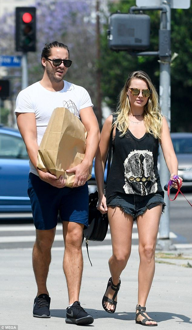 Thing are heating up! Margot Robbie flaunts her toned pins in tiny Daisy Dukes as she goes for a stroll with husband Tom Ackerley during summery LA day on Monday