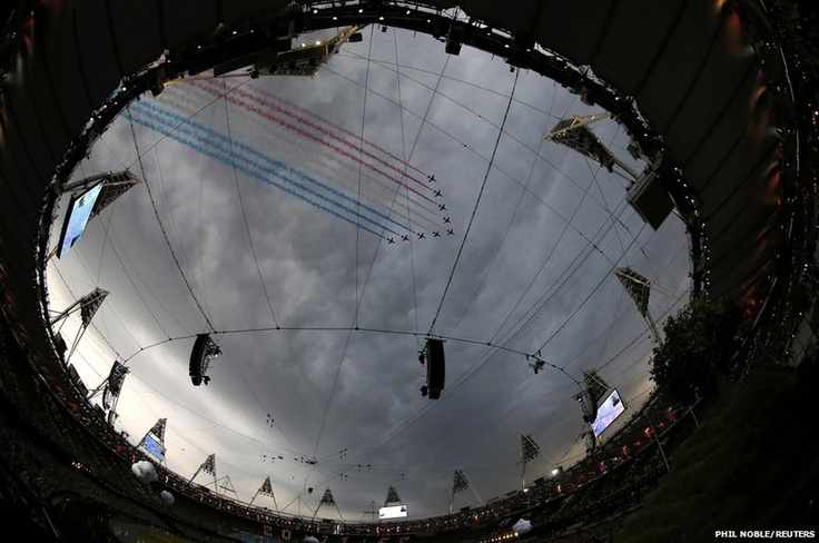 Red Arrows leave coloured smoke trails as they fly over the Olympic Stadium before the opening ceremony of the London 2012 Olympic Games