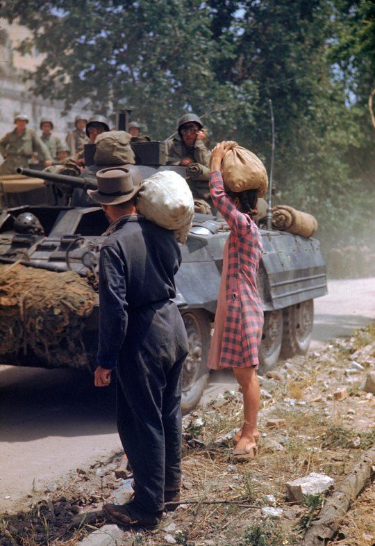 Not published in LIFE. Italians watch American armor pass during the drive towards Rome along the Appian Way, World War II.