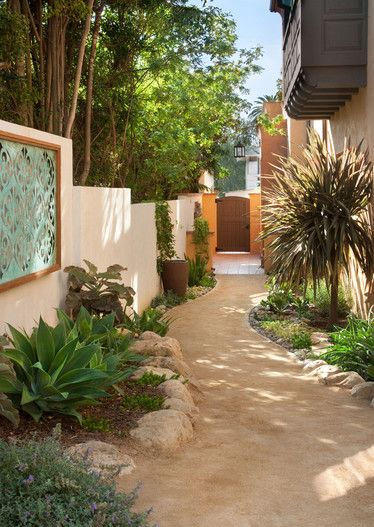 side yard - wall art - tree cordyline - succulents - water wise plants - decomposed granite - stucco wall - boulders - pebbles - pathway - agave attenuata - windy path - wood gate