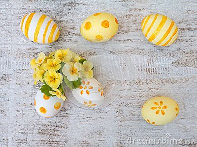 White and yellow decorated easter eggs and primrose flowers composition