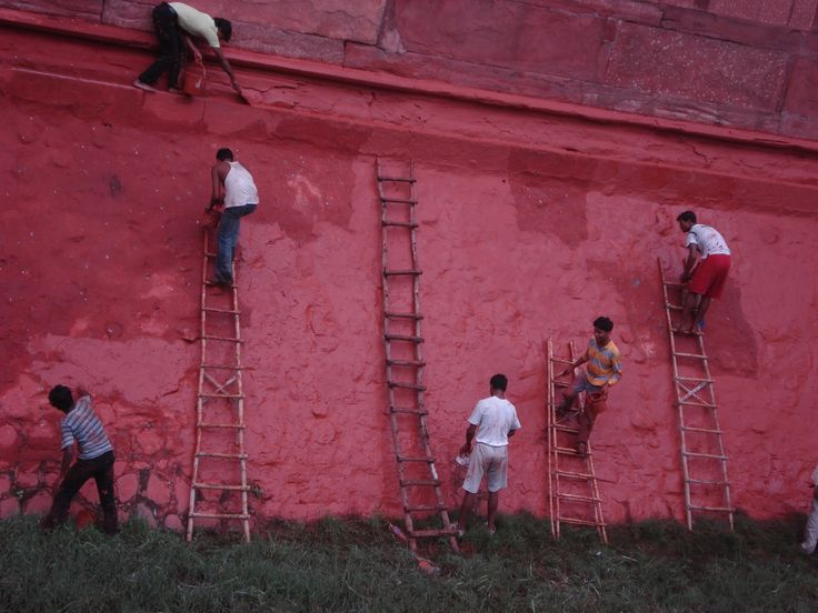 Adding a fresh lick of paint to the Red Fort in Agra, India. I like the feel to this photograph: the home-made ladders, the enthusiam of the boys and the chap on the ledge without any shoes on. His friend in red shorts has no shoes either. Great story.