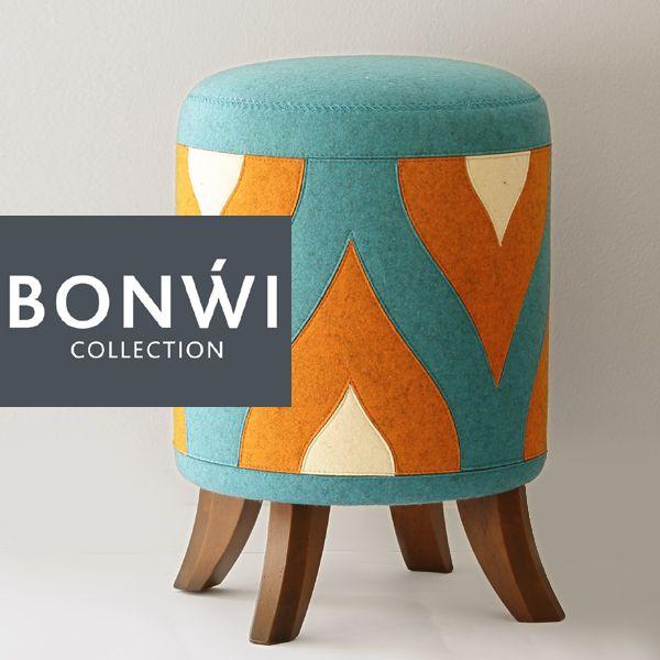 Sitzhocker aus 100 % Wollfilz mit geschwungenen Holzfüssen im antiken Stil.