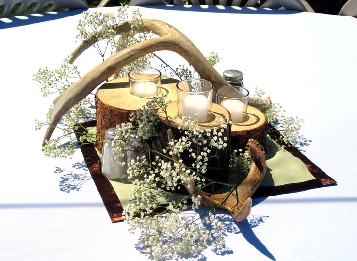 Western theme wedding, logs turned into candle holders with antler decor and baby breath.