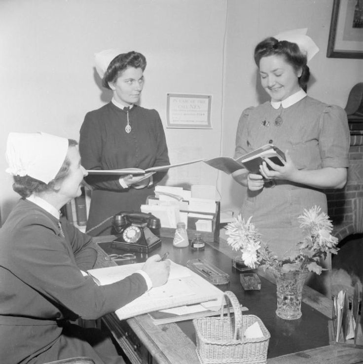 At the training college in Guildford, run by the Queen's Institute of District Nursing, a nurse reports to Matron (seated) on the cases she has visited that day.