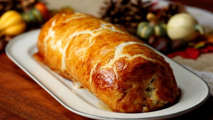 Find a large baking tray and cover with clingfilm. Press the sausage meat into a rectangle then spread the cranberry sauce over the top. Sprinkle with bacon chunks and make…